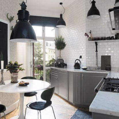 Konyha részletek: szürke fehér konyhabútor, fekete konyhagépek és dekoráció, márvány munkalap, metró csempe, erkély virágokkal